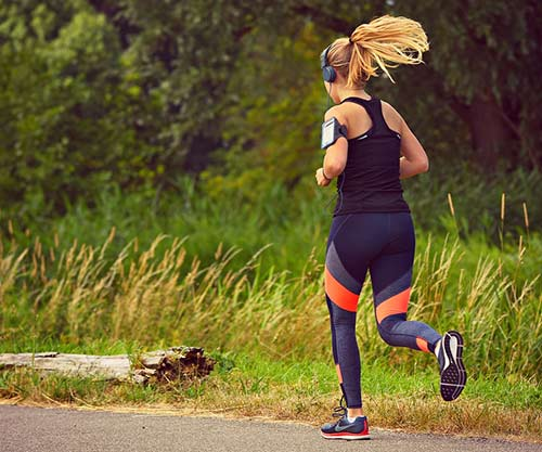 A woman is running with the pedometer on her arm.